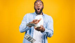 Mann schmeißt mit Geld um sich, um NFT Hype zu symbolisieren.