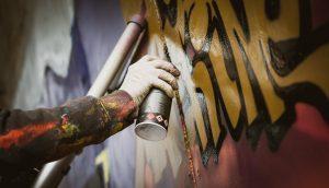 Sprüher besprüht eine Wand mit einer Sprühdose