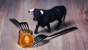 Stapel mit Ethereum-Münzen, daneben eine Bullenfigur und Gabeln (Symbolbild Berlin hard Fork)