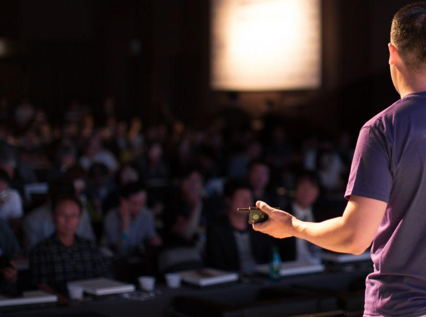 Redner, der vor einem Publikum eine Präsentation hält.