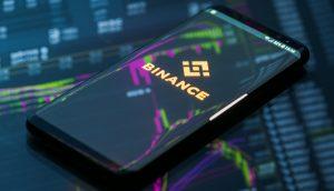Ein Smartphone liegt auf einem Computerbildschirm, der Aktienkurse anzeigt. Auf dem Bildschirm des Smartphones ist das Logo von Binance zu sehen.