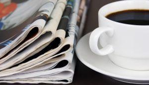 Ein Stapel Zeitungen liegt auf einem Holztisch, daneben steht eine weiße Kaffeetasse auf einem Untersetzer.