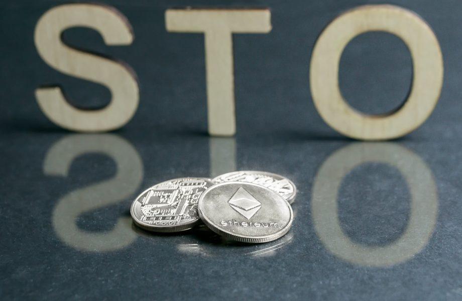 Drei Krypto-Münzen liegen auf einem Tisch. Dahinter stehen die Buchstaben S T O