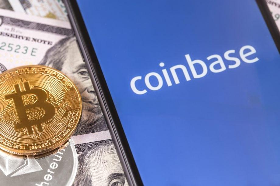Ein Smartphone-Bildschirm zeigt das Coinbase-Logo. Daneben liegen US-Dollar-Noten und eine Bitcoin-Münze.