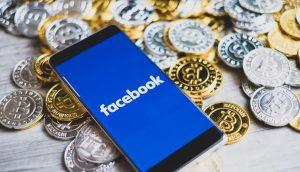 Ein Smartphone liegt auf einem Haufen Bitcoin-Münzen. Auf dem Bildschirm ist das Logo von Facebook zu sehen.