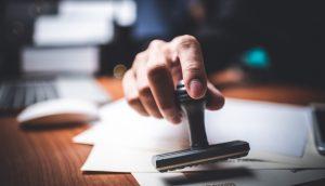 Eine Hand drückt einen Genehmigungstempel auf ein Dokument.