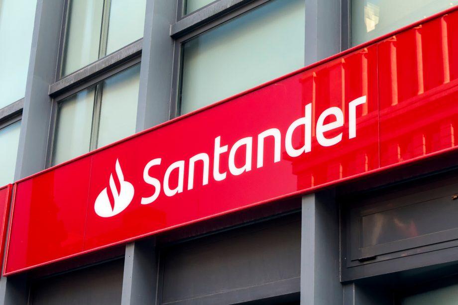 Das Logo der Santander Bank auf einer roten Tafel vor einer Gebäudefassade.
