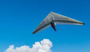 Ein Gleitsegler fliegt durch die Luft. Im Hintergrund ist eine Wolke.