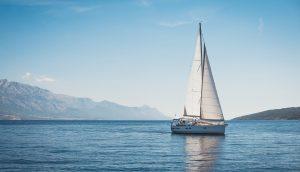 Ein Segelschiff fährt auf stahlendblauem Meer. Am Horizont ist Land in Sicht.