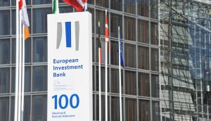 Das Logo der EIB auf einer weißen Tafel vor einem gläsernen Gebäude.