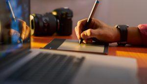 Eine Hand zeichnet etwas auf ein Tablet. daneben steht ein MacBook.