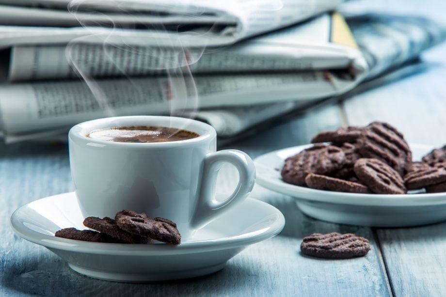 Eine weiße Kaffeetasse samt Untersetzer steht auf einem Tisch. Daneben steht ein Teller mit Gebäck. Dahinter liegt ein Stapel Zeitungen.