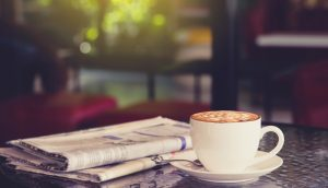 Weiße Kaffeetasse mit Untersetzer steht auf einem Tisch neben einer gefalteten Zeitung. Dahinter ist ein Fenster mit Blick auf den Garten.