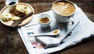 Auf einem Holztisch steht ein kleiner Frühstücksteller. Daneben steht auf einem Tablet eine Kaffeetasse mit Löffel und Zucker. Darunter liegt eine Zeitung.