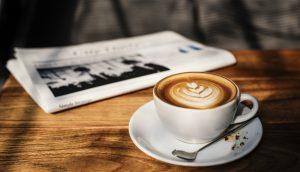 Eine weiße Kaffeetasse mit Untersetzer und Löffel steht auf einem Holztisch. Daneben liegt eine Zeitung.