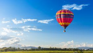 Ein Heißluftballon steigt über einer grünen Landschaft empor.