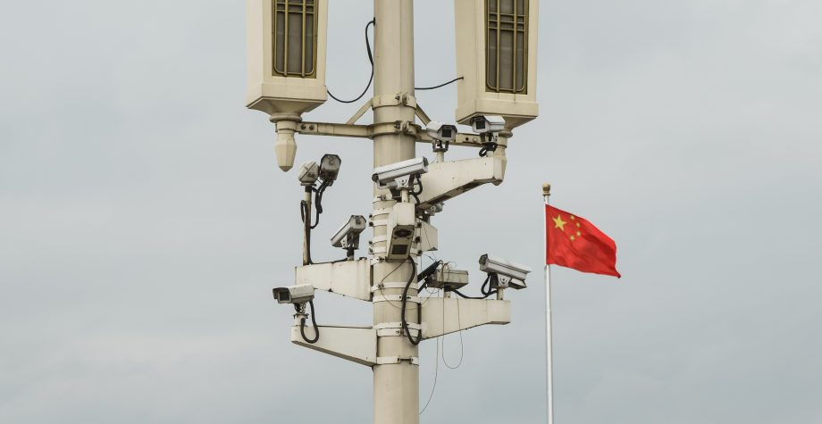 Ein Mast mit Überwachungskameras, daneben weht eine chinesische Flagge.