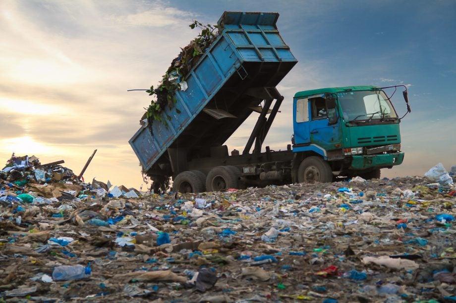 Ein Müllwagen lädt ein Haufen Müll auf einer Deponie ab.