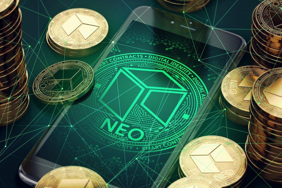 Das Logo der NEO Blockchain auf einem Smartphone Bildschirm. Drumherum liegen NEO-Münzen.