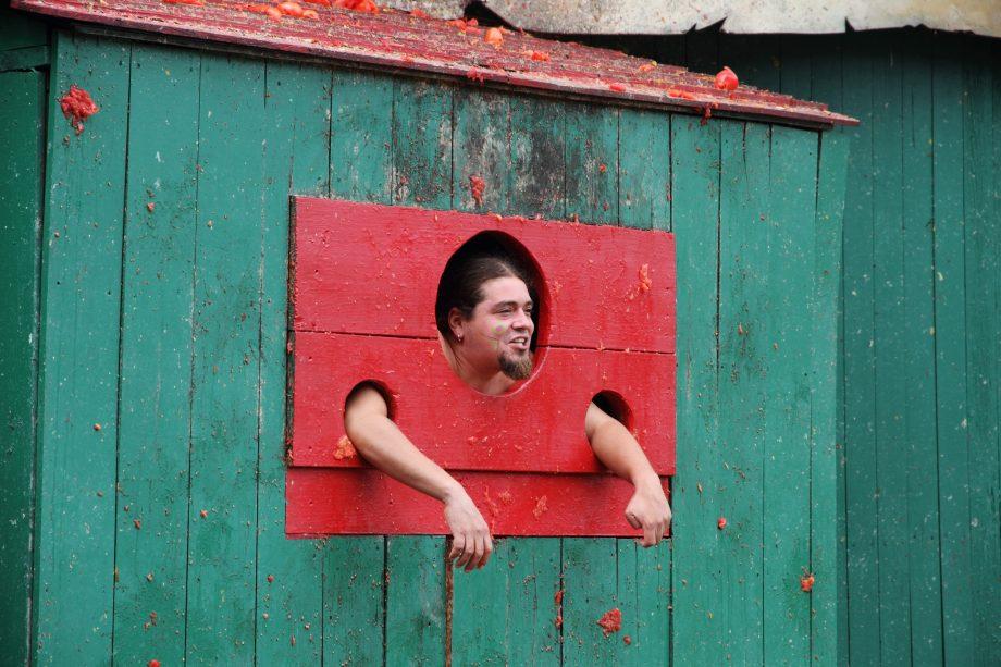 Ein Mann steht am Pranger und wird mit Tomaten beworfen