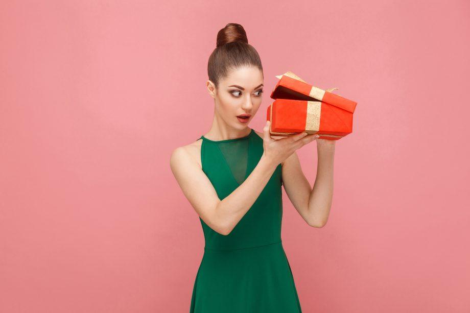 Frau schaut in eine Geschenkebox, was den Inhalt der Blockchain ETF symbolisieren soll.