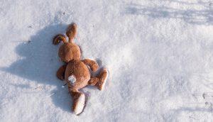 Plüschhase liegt im Schnee