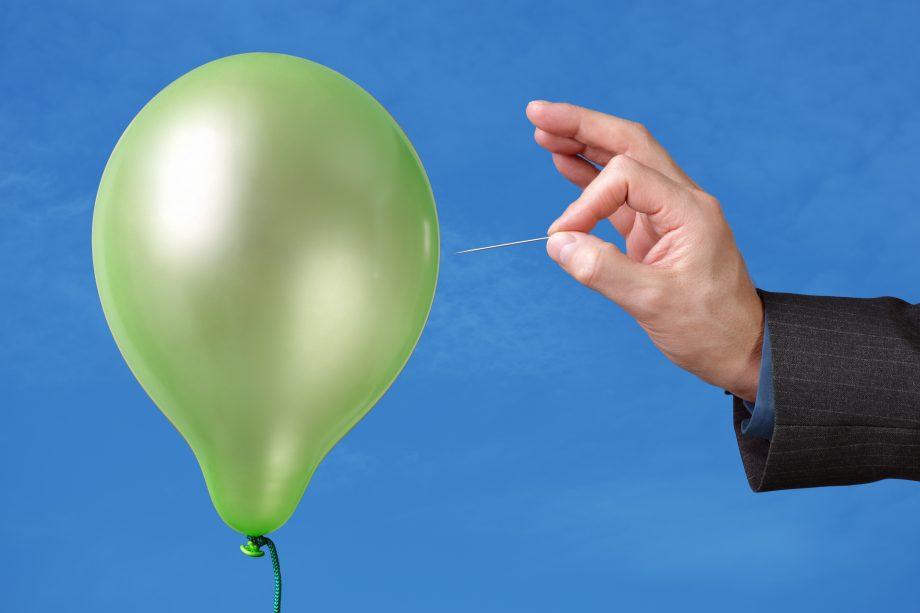 Hand hält Nadel an Luftballon