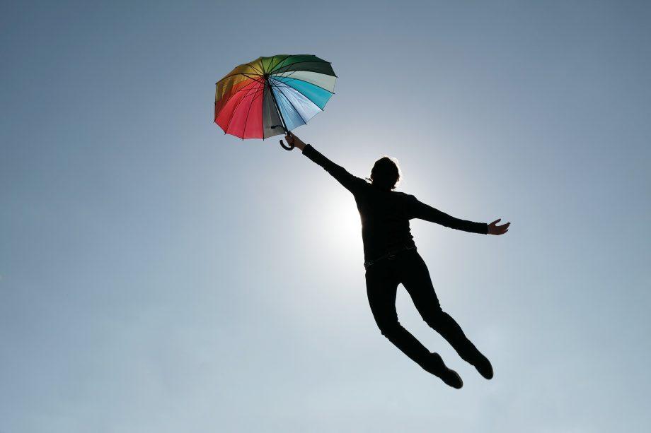 Mensch fliegt mit Regenschirm davon