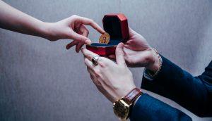 Ein Mann reicht einer Frau einen Bitcoin in einer Ringschachtel