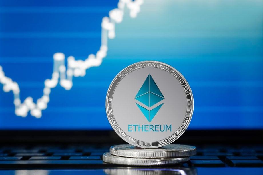 Eine Ether-Münze steht vor einem Kurs-Graphen, der nach oben zeigt.
