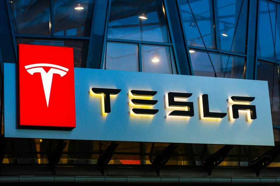 Das Logo von Tesla auf einer gläsernen Gebäudefassade.