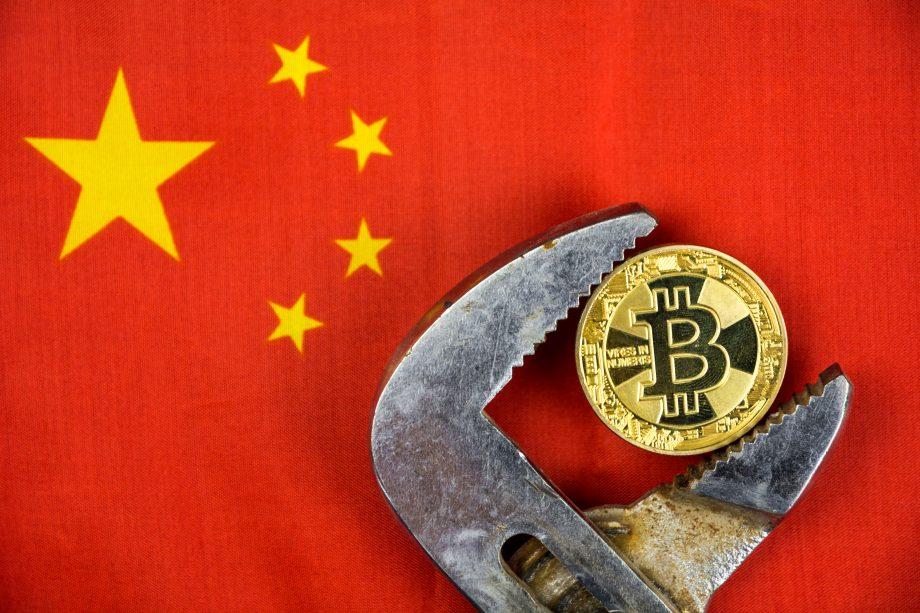 Bitcoin in Rohtzange, im Hitnergrund die chinesische Flagge