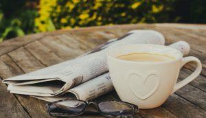 Eine weiße Kaffeetasse steht neben einer Zeitung und einer Brille auf einem Holztisch im Freien.