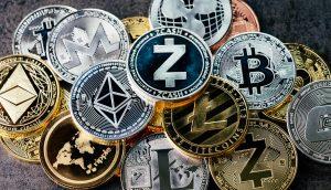 Verschiedene Kryptowährungen liegen als Münzen auf einem Tisch.