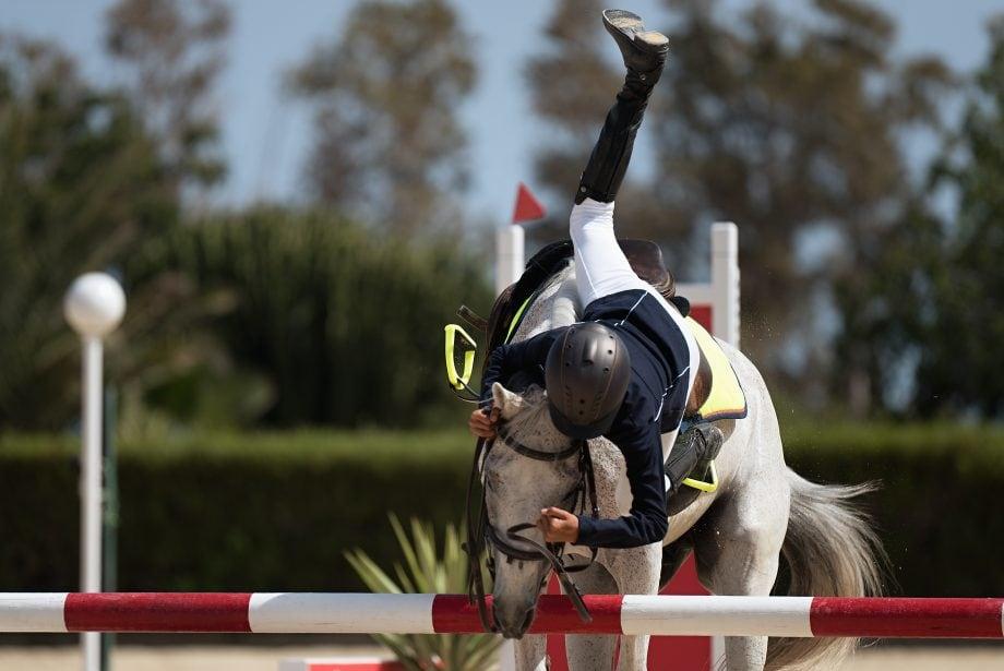 Eine Reiterin stürzt über eine Hürde
