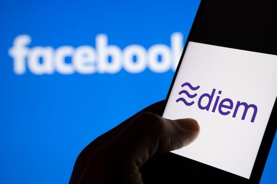 Eine Hand bedient ein Smartphone auf dem das Diem-Logo zu sehen ist. Dahinter ist auf blauem Hintergrund das Logo von Facebook zu sehen.