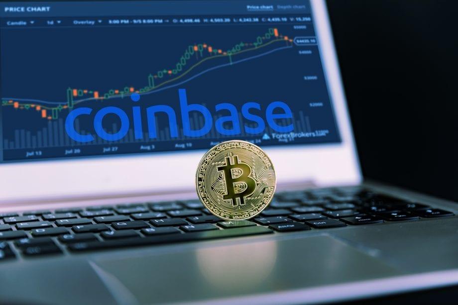 Eine Bitcoin-Münze liegt auf einem Laptop. Dahinter ist Kurs auf der Krypto-Börse Coinbase abgebildet.
