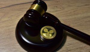 Ein Richterhammer liegt auf dem Tisch. Daneben liegt eine XRP-Münze.