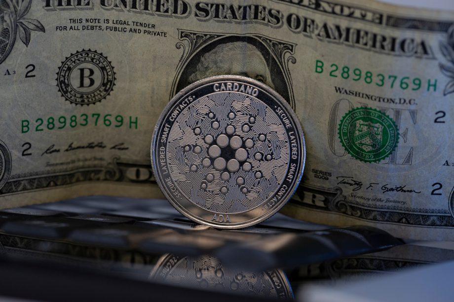 Eine Cardano-Münze steht vor einer US-Dollar-Note.