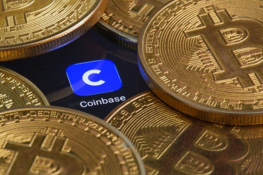 Ein Haufen Bitcoin liegt um ein Display, das das Logo der Coinbase-App zeigt.
