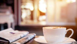 Kaffeetasse steht auf einem Untersetzer auf einem Tisch. Daneben liegen zwei Zeitungen übereinander.
