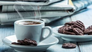 Eine weiße Kaffeetasse steht auf einem Tisch neben einem Teller mit Schokokeksen. Dahinter liegt ein Stapel Zeitungen.