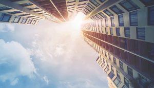 Aufnahme von futuristischen Hochhäusern. Am Himmel scheint die Sonne.