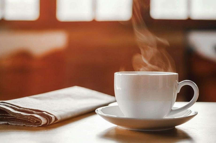 Eine Zeitung und eine Kaffeetasse samt Untersetzer stehen auf einem Tisch. Dahinter fällt Licht durch ein Fenster in den Raum.