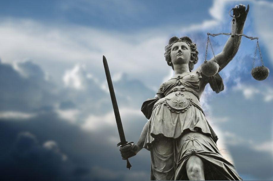 Justizia steht im Vordergrund, dahinter ist ein Wolkenreicher Himmel zu sehen.