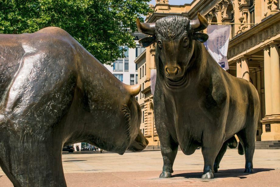 Ein eiserner Bär steht auf einem Platz einem eisernen Bullen gegenüber.
