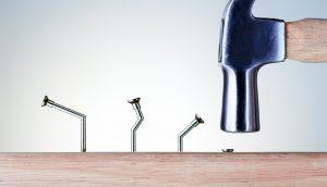 Mit Hammer wird versucht krumme Nägel in Holz zu schlagen als Konzept für Bitcoin Irrtümer.
