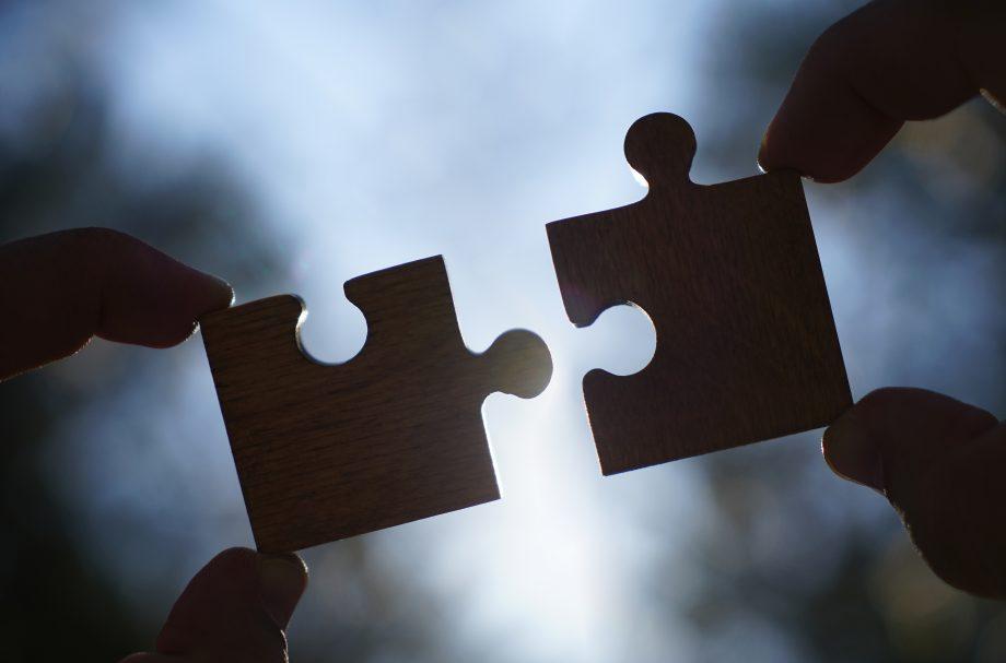 Zwei Hände stecken Puzzlesteine zusammen