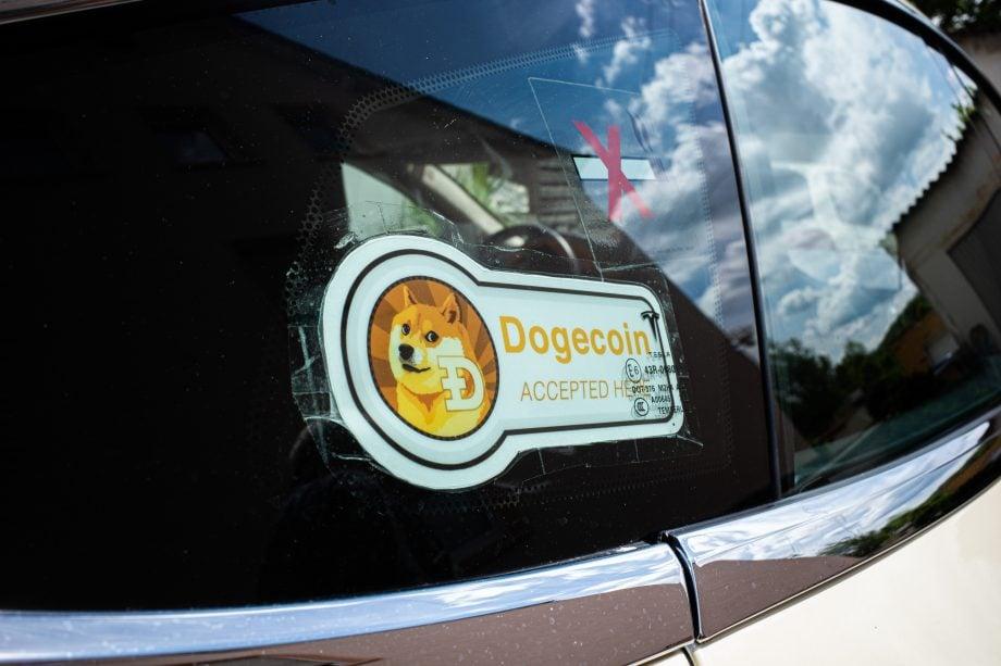 Das Dogecoin-Banner auf einer Autofensterscheibe.