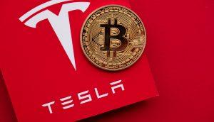 Bitcoin-Münze vor Tesla-Logo